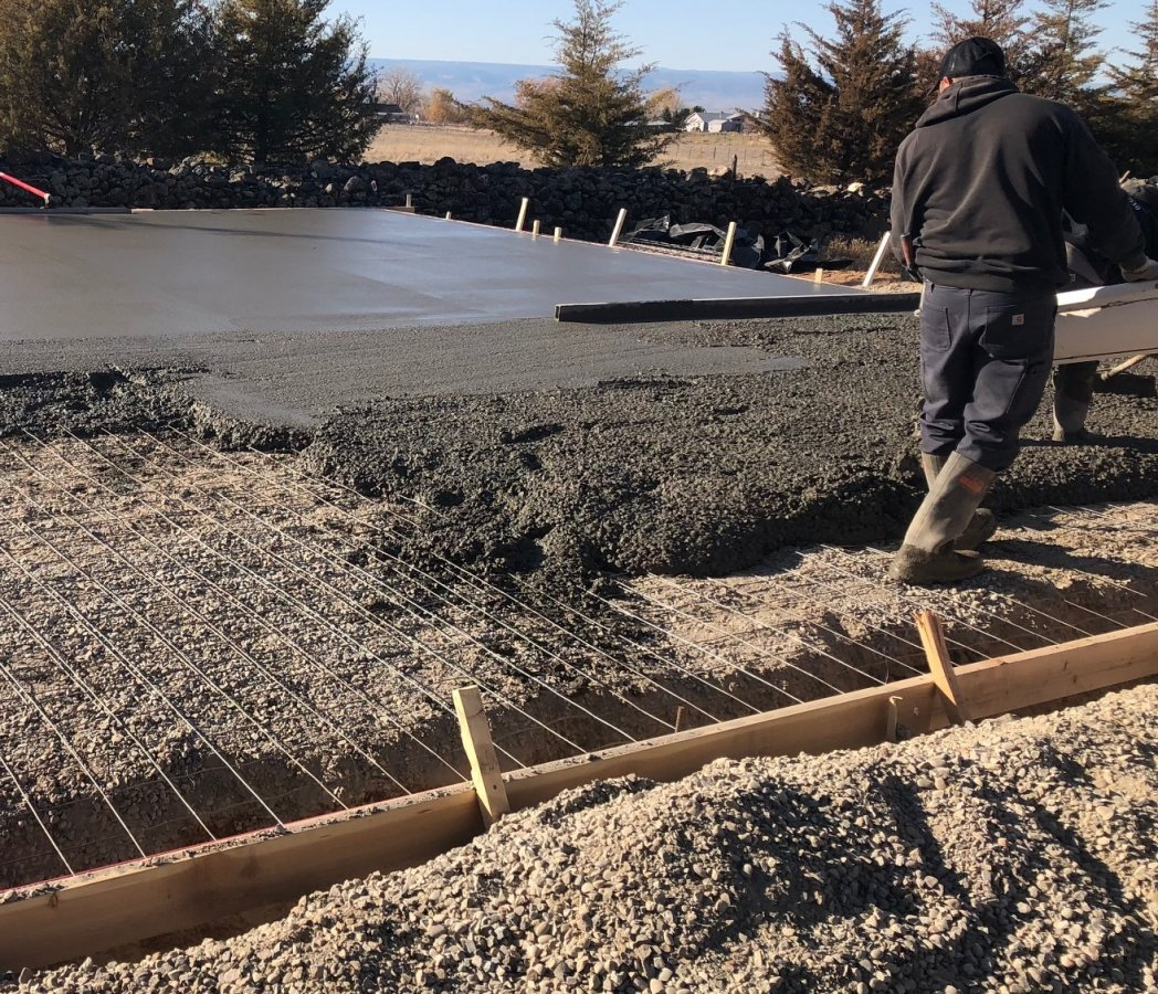 Pouring a monolithic concrete foundation and slab with reinforcement wire.